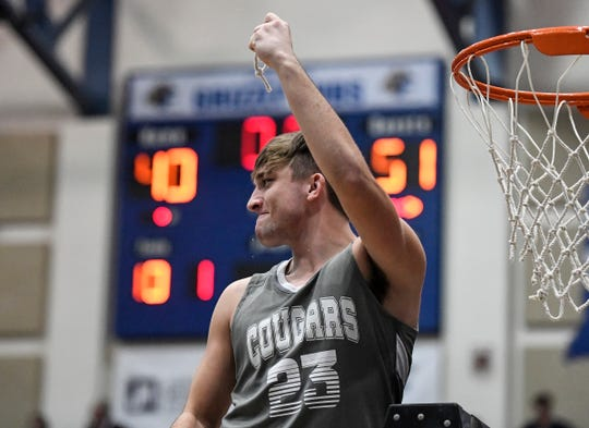 Greenwood Christian Cougars guard Parker Whiteside (23) holds up a piece of net after the win against the Center Grove Trojans at the Johnson County tournament final at Franklin Community High School on Saturday, Jan. 18, 2020. The Greenwood Christian Cougars defeated the Center Grove Trojans 51-40.