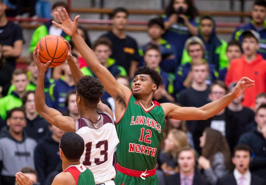 Lawrence North High School senior Tony Perkins (12) goes after the shot of Lawrence Central High School sophomore Tae Davis (13) during the first half of the championship game in the 2020 Marion County Boys' Basketball Tournament, Saturday, Jan. 18, 2020, at Southport High School.