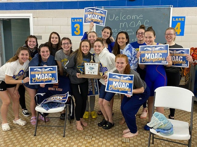 The Ontario girls swim team celebrates its three-peat title in Saturday's Mid-Ohio Athletic Conference meet in its home pool
