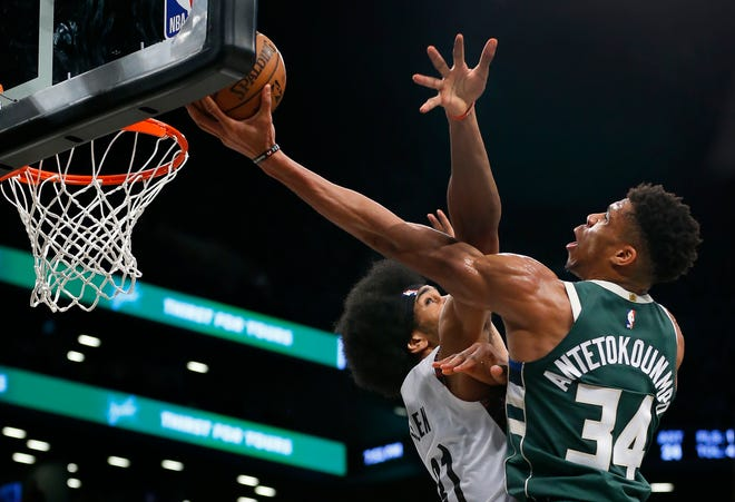 Giannis Antetokounmpo puts up a finger-roll shot next to the rim around Nets center Jarrett Allen during the second half.