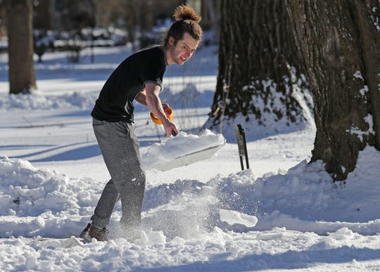 """""""It's hard work"""" explained Tyler Wood defending his decision to wear only a short sleeve shirt in 25-degree weather as he shovels near his Whitefish Bay home on North Lake Drive in Milwaukee on Sunday, Jan. 19, 2020."""