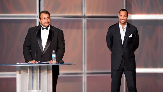 "In this 2008 photo provided by WWE, Inc., Rocky ""Soul Man"" Johnson, left, speaks at his WWE Hall of Fame induction ceremony, as his son, Dwayne ""The Rock"" Johnson watches. Rocky Johnson died Wednesday, Jan. 15, 2020. He was 75. (WWE, Inc. via AP)"
