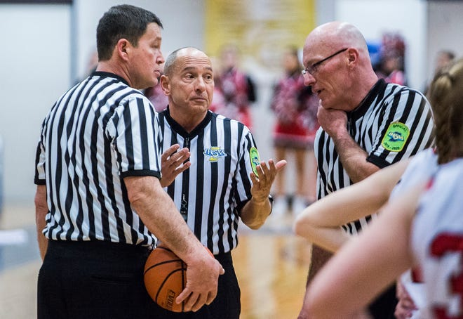 FILE -- Jay Petty (left) talks with two other sports officials as Yorktown faces off against Wapahani during the Delaware County girls basketball championship game at Delta High School Saturday, Jan. 18, 2020.