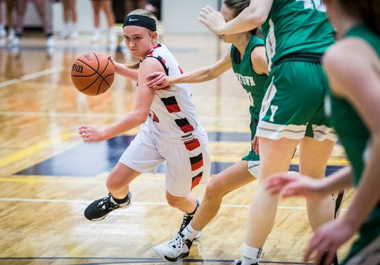 FILE -- Wapahani's Madison Thompson dribbles past a pair of Yorktown defenders during their county championship game at Delta High School Saturday, Jan. 18, 2020.