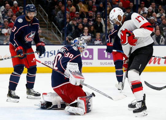 Columbus Blue Jackets goalie Elvis Merzlikins, center, of Latvia, makes a stop in front of New Jersey Devils forward Wayne Simmonds, right, as Blue Jackets defenseman Seth Jones moves in during the first period an NHL hockey game in Columbus, Ohio, Saturday, Jan. 18, 2020.