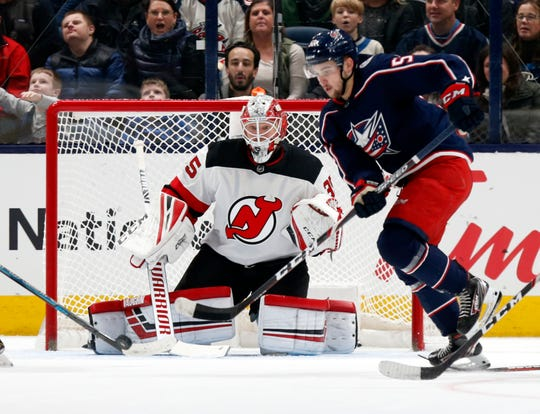 New Jersey Devils goalie Cory Schneider, left, watches the puck behing Columbus Blue Jackets forward Emil Bemstrom, of Sweden, during the first period an NHL hockey game in Columbus, Ohio, Saturday, Jan. 18, 2020. The Blue Jackets won 5-0.