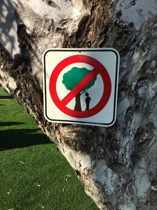 A sign a man posted on the tree in his yard, to prevent people from (ahem) fertilizing it.