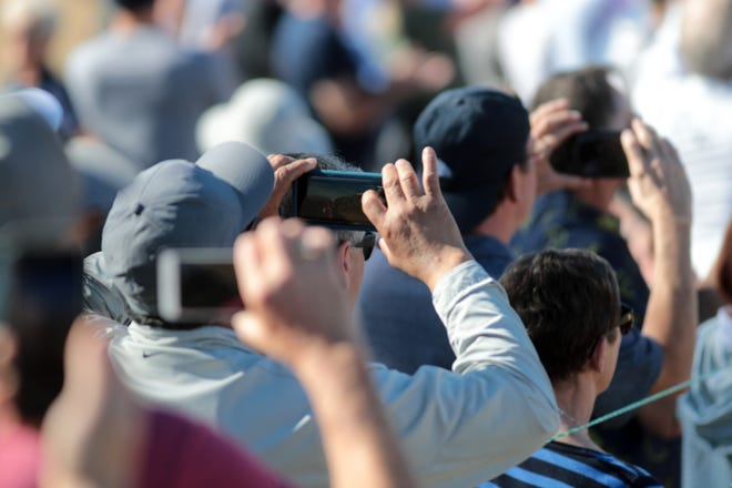 Spectators take photos of the action on the first hole at PGA West in La Quinta during the American Express golf tournament, January 19, 2020.