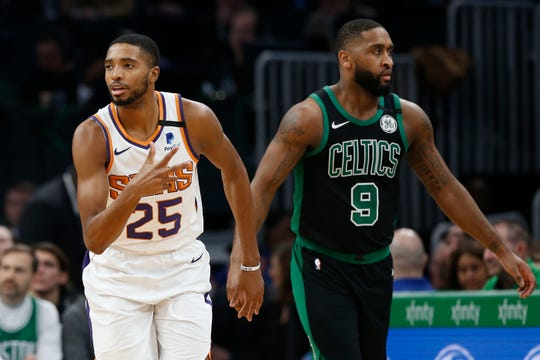 Jan 18, 2020; Boston, Massachusetts, USA; Phoenix Suns forward Mikal Bridges (25) signals three after hitting a three point shot as Boston Celtics guard Brad Wanamaker (9) walks away during the second quarter at TD Garden. Mandatory Credit: Winslow Townson-USA TODAY Sports