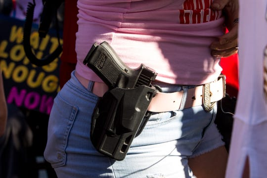 A protestor carries a gun on her belt during the Women's March Phoenix Rally in Arizona in January. Other states to embrace permitless carry include Alaska and Arkansas.