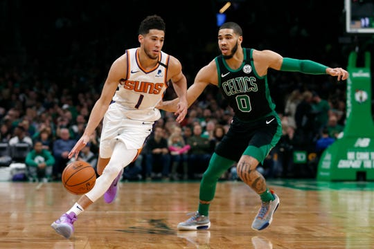 Phoenix Suns guard Devin Booker (1) drives past Boston Celtics forward Jayson Tatum (0) during the first half of an NBA basketball game, Saturday, Jan. 18, 2020, in Boston. (AP Photo/Mary Schwalm)