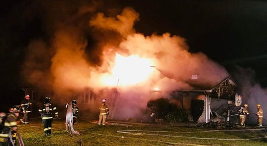 Firefighters work to control a fire that began in an attached garage on Old York Road in Monkton, Harford County.