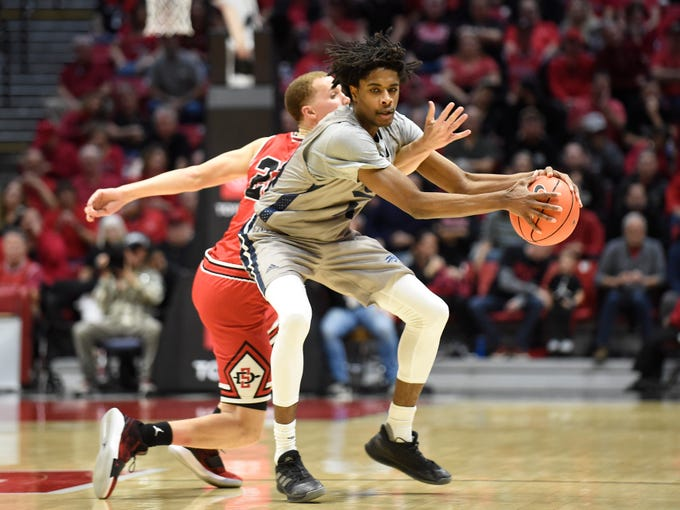 San Diego State guard Malachi Flynn, left, fights for the ball with Nevada guard Lindsey Drew, right, during the second half of an NCAA college basketball game Saturday, Jan. 18, 2020, in San Diego. (AP Photo/Denis Poroy)