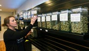 In this Oct. 26, 2018, photo, Diana Calvert, River City Retail Marijuana Dispensary manager stocks the shelves with product in Merlin, Ore. (Timothy Bullard/The Daily Courier via AP)