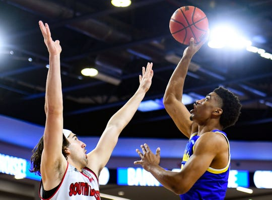 Hunter Goodrick of USD men tries to block a shot by Alou Dillon of SDSU on Sunday, Jan. 19, at the Sanford Coyote Sports Center in Vermillion.