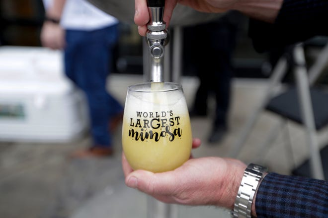 """Three thousand ounces of """"Tallahassee's largest mimosa,"""" the unofficial world record, are served in souvenir glasses at Madison Social Sunday, Jan. 19, 2020."""