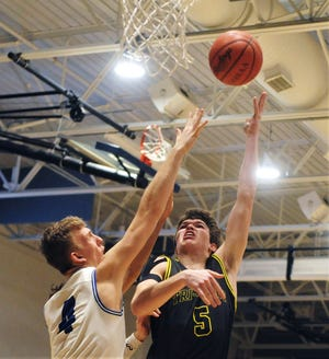 Keaton Williams goes up for a shot in the lane over Zanesville's Shelton Redman during the Scotties' 64-52 win on Saturday night at Winland Memorial Gymnasium.