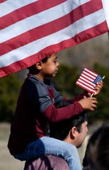 Kaden Ferguson, 6, plays with his miniature American flag while sitting atop the shoulders of his father, Sam. The pair were waiting for the start of Monday's Martin Luther King Jr. march across the MLK bridge in east Abilene.