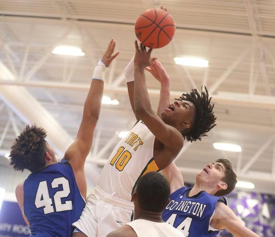 Taft forward Rayvon Griffin (10) drives to the basket against Covington Catholic players Chandler Starks and Noah Hupmann during the King Classic, Sunday, Jan. 19, 2020.