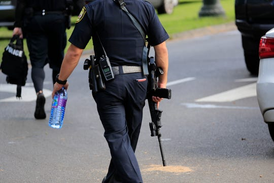 A Honolulu police officer carries an assault rifle near the scene of multiple house fires in a Diamond Head neighborhood, Sunday, Jan. 19, 2020, in Honolulu, following a shooting in which two police officers were shot. (AP Photo/Marco Garcia)
