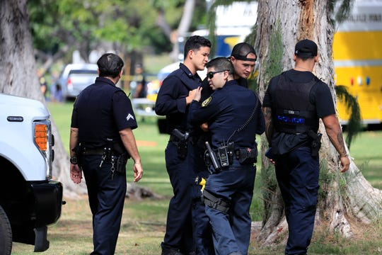 Honolulu police officers gather near the scene of a shooting near Diamond Head State Monument on Sunday, Jan. 19, 2020, in Honolulu. (AP Photo/Marco Garcia)