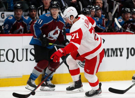 Red Wings center Dylan Larkin, front, picks up a loose puck as Avalanche left wing Matt Calvert looks on in the second period on Monday, Jan. 20, 2020, in Denver.