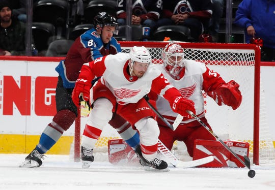Red Wings defenseman Alex Biega, front, clears the puck from in front of the net as Avalanche center Vladislav Kamenev, left, and Detroit goaltender Jimmy Howard, right, look on in the second period on Monday, Jan. 20, 2020, in Denver.