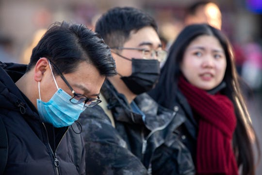 Travelers wear face masks as they walk outside of the Beijing Railway Station in Beijing on Monday.
