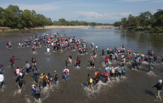 Central American migrants cross the Suchiate River by foot from Tecun Uman, Guatemala, to Mexico, Monday, Jan. 20, 2020.