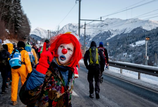 A man dressed as a clown is part of hundreds of climate protesters who are on a three-day  protest march from Landquart to Davos pass the city of Klosters, Switzerland, Monday, Jan. 20, 2020.