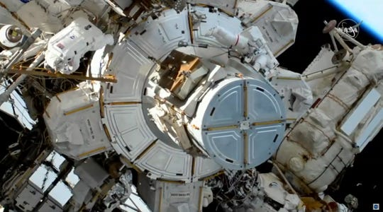 In this image take from NASA video, astronauts Christina Koch, left, moves away as Jessica Meir, right, exits a hatch as they prepare to install batteries for the International Space Station's solar power grid during a space walk, Monday, Jan. 20, 2020.