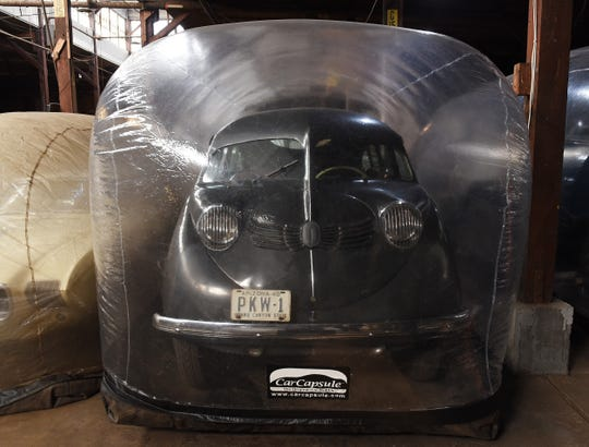 A 1935 Stout Scarab car is stored at Fort Wayne inside a protective plastic car capsule.
