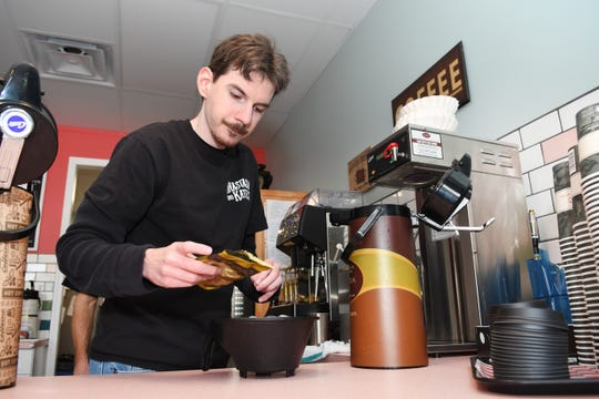 Ian Edgar pours coffee grounds at Anastasia and Katie's Coffee Shop and Cafe, Livonia, as he makes a pot of coffee for customers as part of MI Work Matters program.
