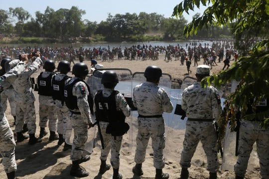 Mexican National Guards stand on the bank of the Suchiate River where Central American migrants are crossing from Guatemala, near Ciudad Hidalgo, Mexico, Monday, Jan. 20, 2020.