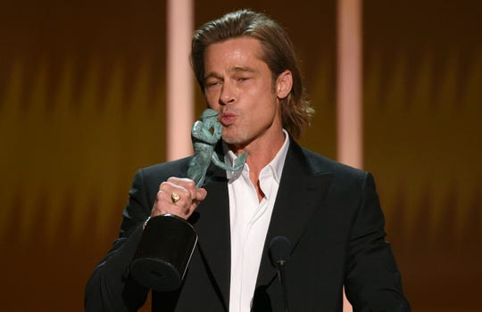 """Brad Pitt kisses """"The Actor"""" statuette as he accepts the award for outstanding performance by a male actor in a supporting role for """"Once Upon a Time in Hollywood"""" at the 26th annual Screen Actors Guild Awards at the Shrine Auditorium & Expo Hall on Sunday."""
