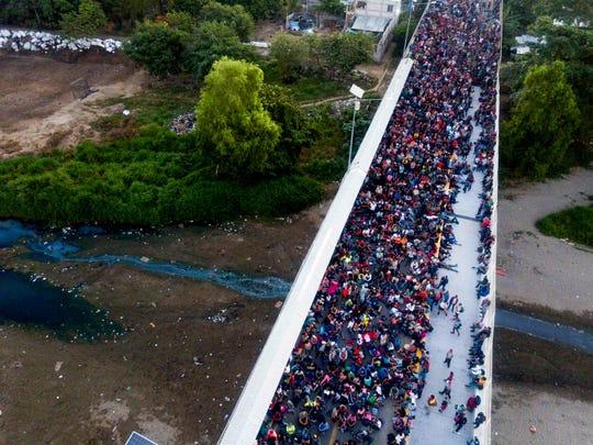 Migrants gather at the bridge spanning the Suchiate River in Tecun Uman, Guatemala, Monday, Jan. 20, 2020.