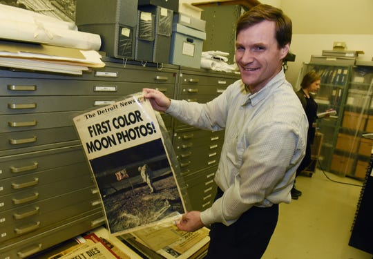 Jeremy Dimick, director of Collections for the Detroit Historical Society, holds an August 5, 1969, front page of the Detroit News celebrating the first photos taken on the moon.