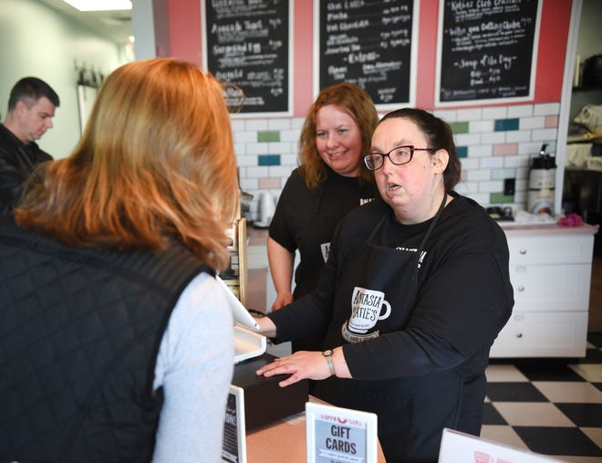 Christina Victor (center), manager, Anastasia and Katie's Coffee Shop and Cafe, works with Danielle Donaldson, who works the front register, as she assists customers.