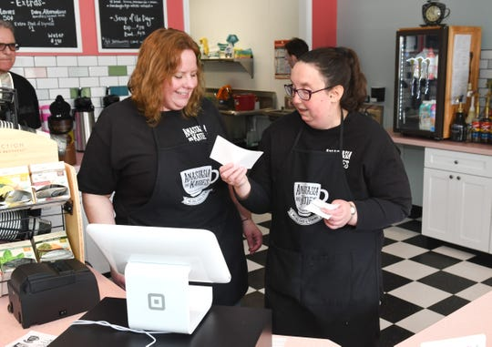 Christina Victor (left), manager,  Anastasia and Katie's Coffee Shop and Cafe, assists Danielle Donaldson who works the front register  as part of a MI Work Matters program, a nonprofit organization dedicated to providing employment opportunities for people with developmental disabilities.