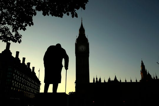 A statue of Winston Churchill is silhouetted against the Houses of Parliament and the early morning sky in London, Friday, June 24, 2016.