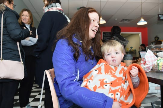 Abby Bernhardt of Dearborn gives her son Tony a bagel with cream cheese at Anastasia and Katie's Coffee Shop and Cafe as she supports the MI Work Matters program.