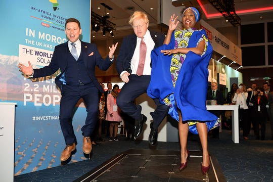 Britain's Prime Minister Boris Johnson, center, visits the Pavegen stand, a company that converts footsteps into energy, at the Innovation Zone during the UK Africa Investment Summit in London, Monday Jan. 20, 2020.