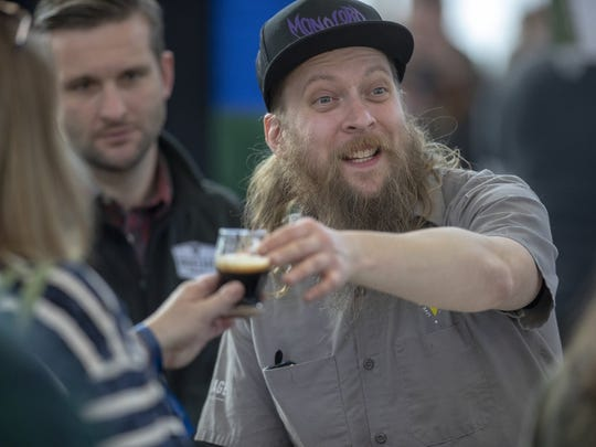Corey Patterson, with Lafayette's Brokerage Brewing Co., serves customers at the 2019 Brewers of Indiana Guild Winterfest.