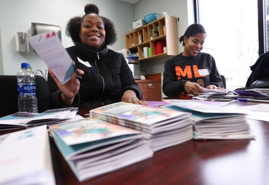 U of L students Tyra Kemp, left, and Spechelle Goodwin fold brochures at the Americana Community Center in Louisville on Monday. They were volunteering as part of the MLK Day of Service.