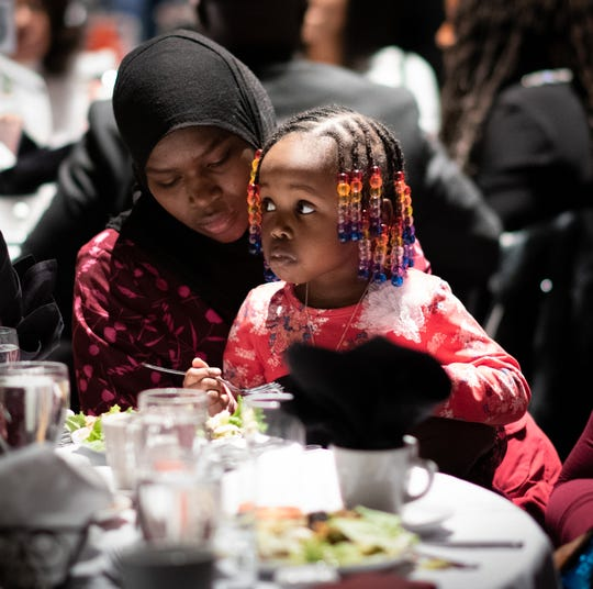 Chiffa Hassan, 17, a student at Everett High School, holds sister Tysir Adam, 3, Monday, Jan. 20, 2020, during the 35th Annual Martin Luther King Jr. Day of Celebration Luncheon at the Lansing Center. Hassan and her family are refugees from Sudan.  Chiffa was a 2020 scholarship award winner.  Her older sister won a scholarship last year.