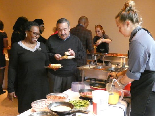 Arrita McGary, left, and David Kasmenn, middle, wait in line for omelettes at the 13th annual Peace and Freedom Breakfast in honor of Martin Luther King Jr.