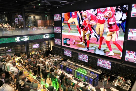 Packers fans watch as the 49ers celebrate one of their touchdowns on a giant TV screen at Mecca Sports Bar and Grill in Milwaukee