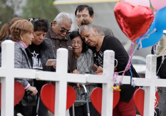 Family and friends gather around a makeshift memorial on Nov. 10, 2017, for the victims of the First Baptist Church shooting at Sutherland Springs Baptist Church in Sutherland Springs, Texas.