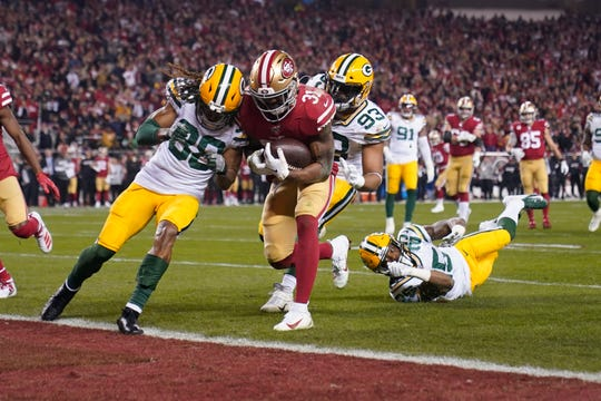 San Francisco 49ers running back Raheem Mostert, center, scores a touchdown next to Green Bay Packers cornerback Tramon Williams (38) during the second half of the NFL NFC Championship football game Sunday, Jan. 19, 2020, in Santa Clara, Calif. (AP Photo/Tony Avelar)