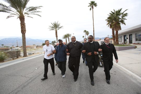 Clergy members walk arm-in-arm during the Martin Luther King Jr. Unity Walk organized by the Desert Hot Springs Christian Ministerial Fellowship. The procession went from the Desert Hot Spring Police Department to the First Community Baptist Church on Jan. 20, 2020.